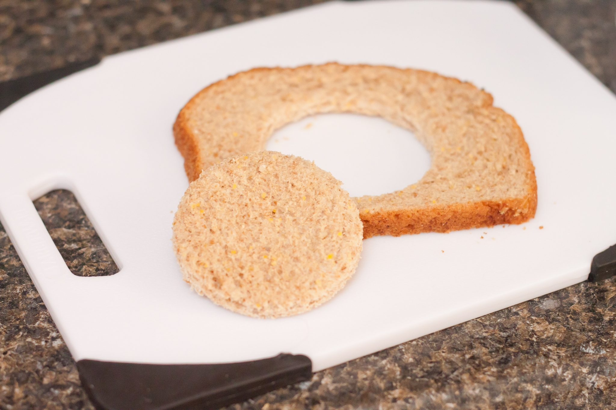 Cut a hole in the center of the bread slice.